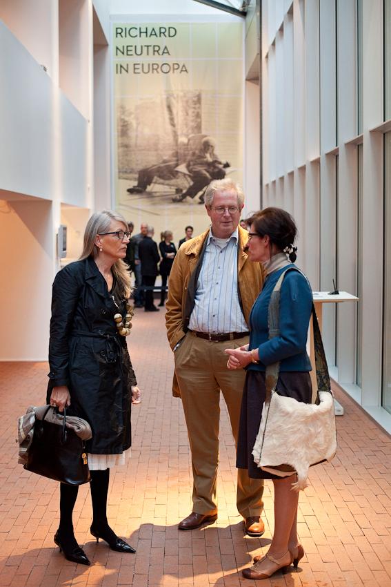 """Freitagabend wurden im Museum MARTa Herford drei verschiedene Architektur-Ausstellungen eroffnet. Vernissagebesucher vor dem Plakat zur Ausstellung """"Richard Neutra in Europa. Bauten und Projekte 1960 bis 1970""""."""