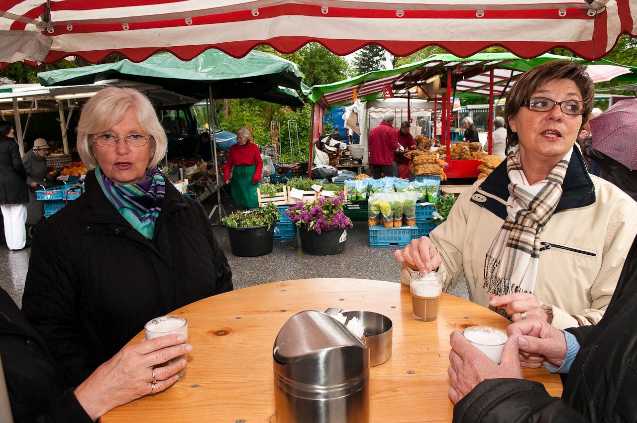 Wochen-Markttag am 7.5.2010 in Refrath, Bergisch Gladbach, fotografiert von Ulla Franke. Plauderstunde -trotz Regen- am Cappucino-Stand von Johannes Putz in Refrath. Die Damen unterhalten sich jeweils mit ihren nicht zu sehenden Nachbarn. Im Hintergrund sieht man Marktstände.