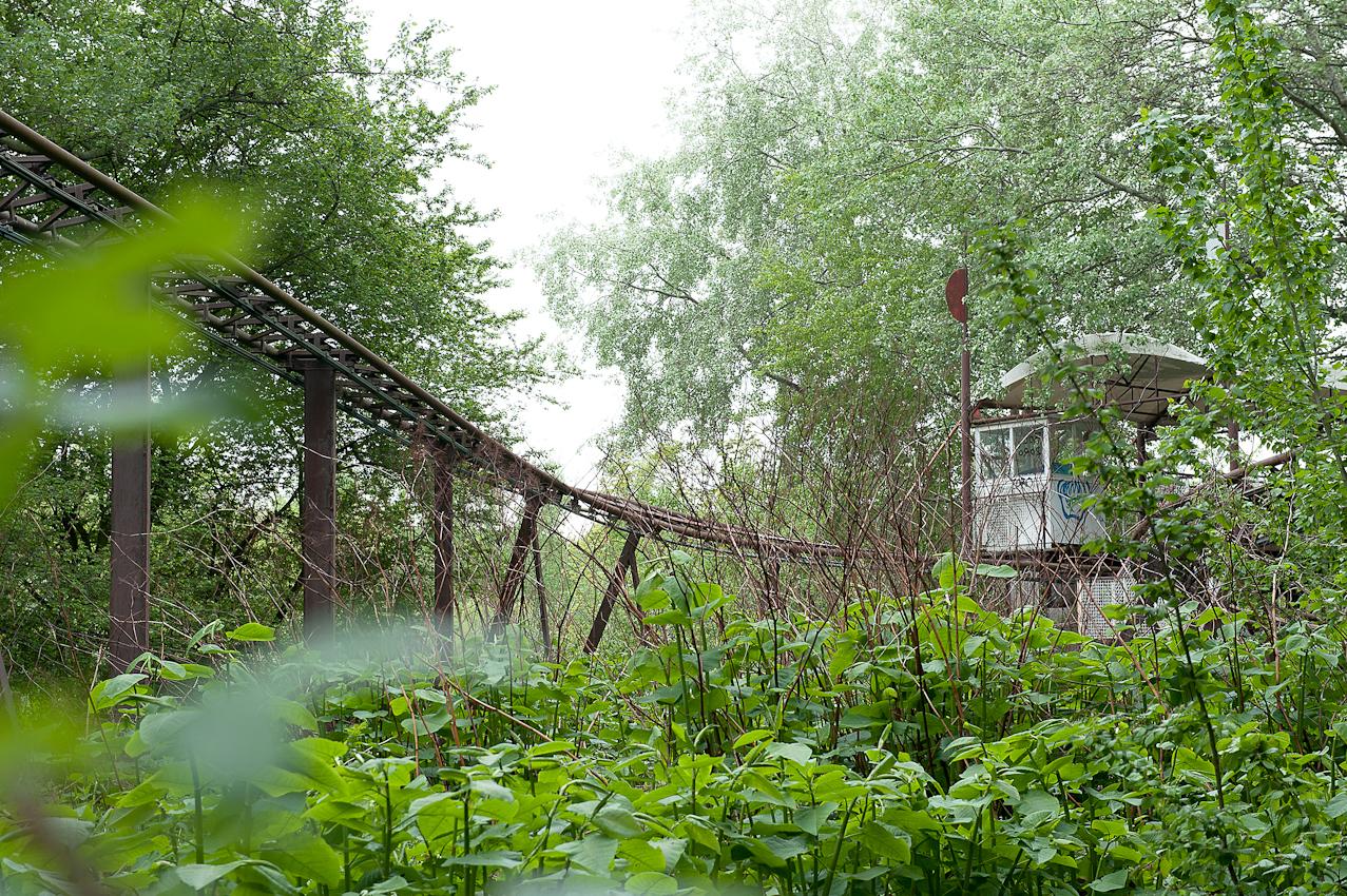 """Spreepark Planterwald. Der Vergnugungspark - im Norden des Planterwaldes gelegen- wurde 1969 als VEB Kulturpark Planterwald eröffnet.Er war der einzige ständige Vergnügungspark der DDR. Zu DDR-Zeiten kamen bis zu 1,7 Millionen Besucher jährlich. 1992-2001 als Spreepark geführt. Seit dem Jahr 2002 wurde der Park nicht mehr fur Besucher geöffnet. Beschreibung Motiv:  Der Spreeblitz,still.Die Fakten:  Baujahr: 1987/Herkunft: 1987 bis 1991 """"Mirapolis"""" (Frankreich) unter dem Namen """"Le Dragon des Sortileges""""/Achterbahn-Kategorie: Powered Coaster/Achterbahn-Typ: Stahl - Sit Down/Anzahl der Zuge: 1 Lok und 9 Waggons/Personen pro Zug: 38 Personen/Kapazität: 1.800 Personen pro h/Geschwindigkeit: 45km pro h/ Spreeblitzzug  seit dem 05.November 2001 im Bahnhof"""