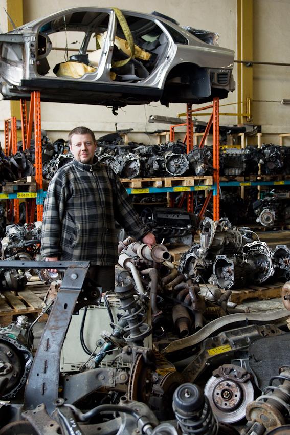 Dieser Haendler aus Polen kauft und verkauft gebrauchte Ersatzteile fuer alle Automarken, hauptsaechlich Motoren und Getriebe. Hier steht er inmitten seiner Maschinen, die er wohlgeordnet in Regalen und auf dem Boden lagert. In den Lagerhallen und auf den Gewerbeplaetzen am Hammer Deich im Stadtteil Hamm-Sued arbeiten Menschen aus verschiedensten Laendern. Die meisten Waren sind fuer den Export bestimmt.