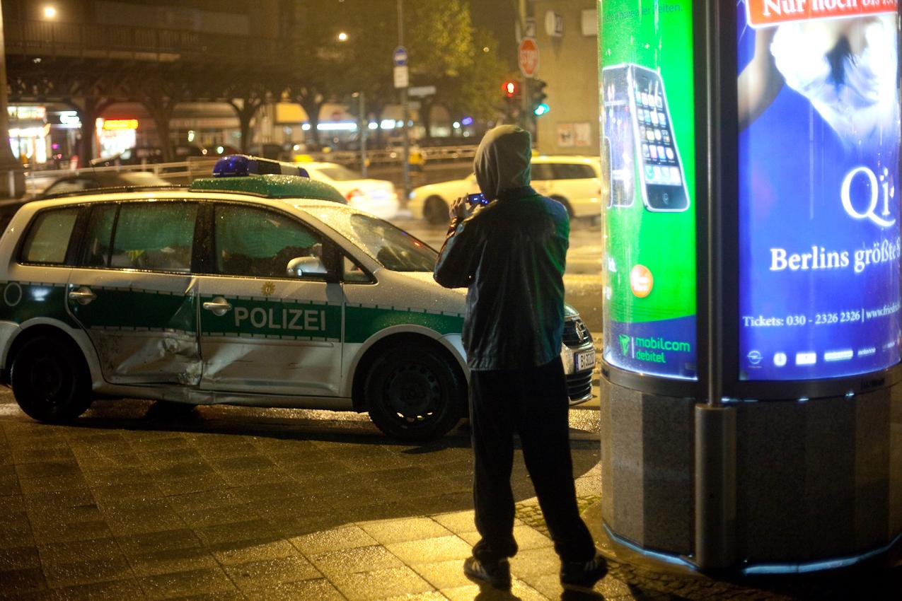 Berlin, 7. Mai 2010, 0.51 Uhr morgens. Potsdamerstr., Commerzbankfiliale hoehe Buelowstr. Ein Berliner Polizeiwagen ist auf dem Weg zum Einsatz von einem Privatpkw frontal gerammt worden. Jugendliche machen Handyfotos von dem Auto. Grund des Einsatzes: Es wurden verdaechtige Personen im Vorraum gemeldet.