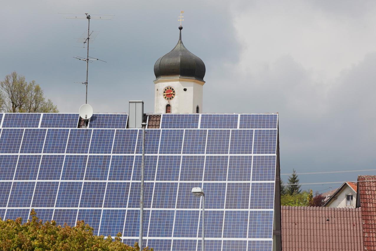 In der Ortsmitte von Hasenweiler, einem Ortsteil von Horgenzell im Kreis Ravensburg, Oberschwaben, kombinieren sich moderne Energietechnologie mit historischer und neuer Weltsicht: Kirchturm der Katholischen Pfarrkirche Maria Geburt,