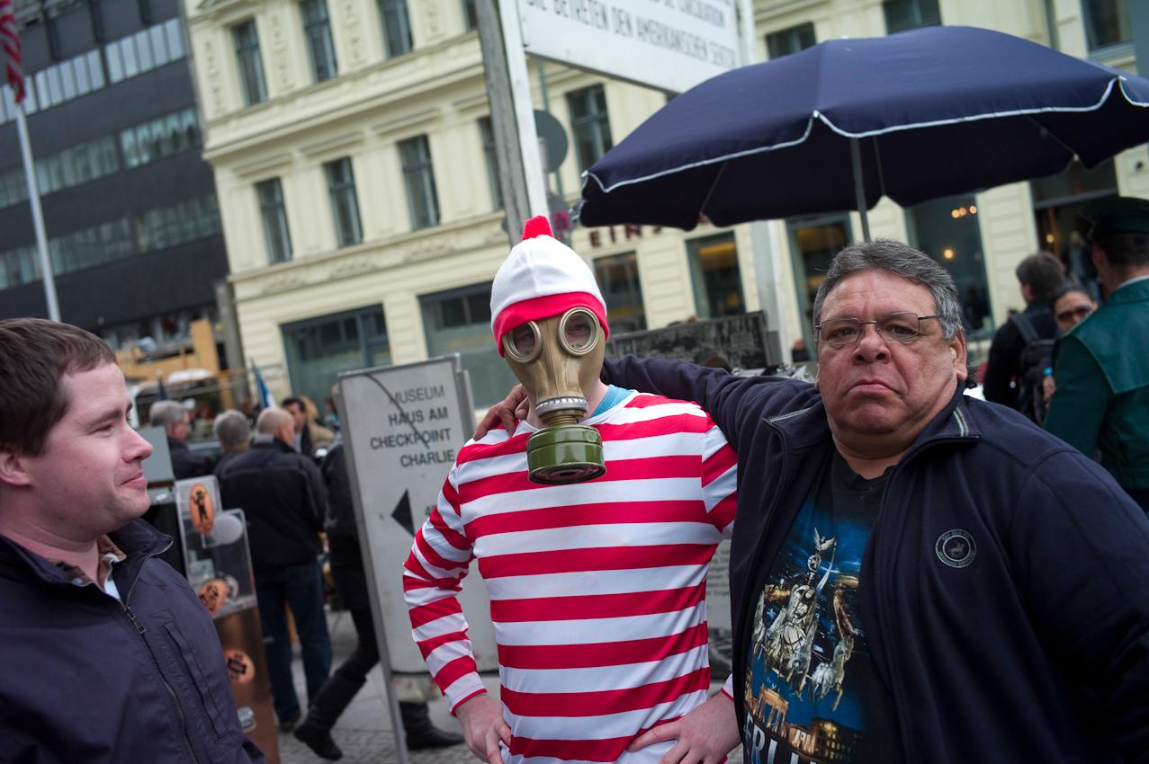 Touristen in Berlin. Ein Tourist hat gerade von einem fliegenden Händler (rechts) eine DDR Gasmaske am Checkpoint Charlie gekauft.