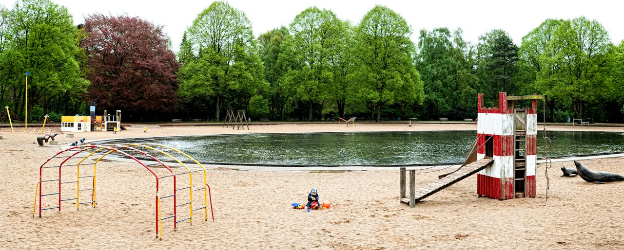 Beobachtung der Erkundung des maritimen Kinderspielplatz im Stadtpark Hamburg/Winterhude durch ein Kleinkind. Eingerahmt von verschiedenen Spielgerüsten und einem künstlichen See, spielt das Kleinkind 'Ben' im Sand mit seinen Spielsachen. Die Panoramaaufnahme des Spielplatzes wurde am 7.5.2010 um 15:53h gemacht.