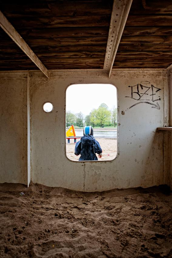 Beobachtung der Erkundung des maritimen Kinderspielplatz im Stadtpark Hamburg/Winterhude durch ein Kleinkind. Aus dem inneren eines Spielgerüstes in Form eines Schiffs, sieht man das Kleinkind 'Ben', welches auf einen künstlichen See schaut. Im Hintergrund ist ein Spielgerat in Form eines Surfboards zu sehen. Die Aufnahme wurde am 7.5.2010 um 16:13h gemacht.