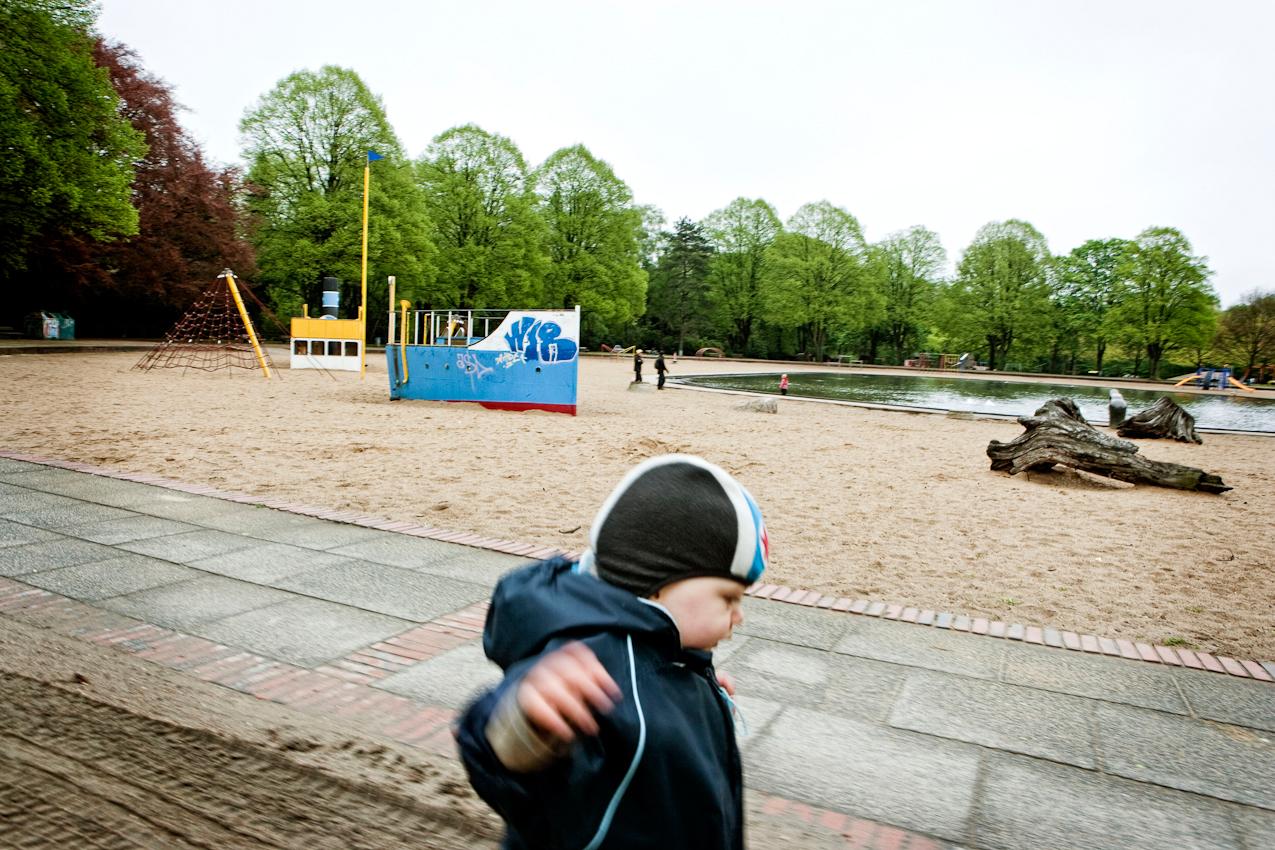 Beobachtung der Erkundung des maritimen Kinderspielplatz im Stadtpark Hamburg/Winterhude durch ein Kleinkind. Das Kleinkind 'Ben' lauft mit ausgebreiteten Armen am Rand des Spielplatzes entlang. Im Hintergrund sind maritime Spielgerüste, ein See und Bäume zu sehen. Die Aufnahme wurde am 7.5.2010 um 16:42h gemacht.