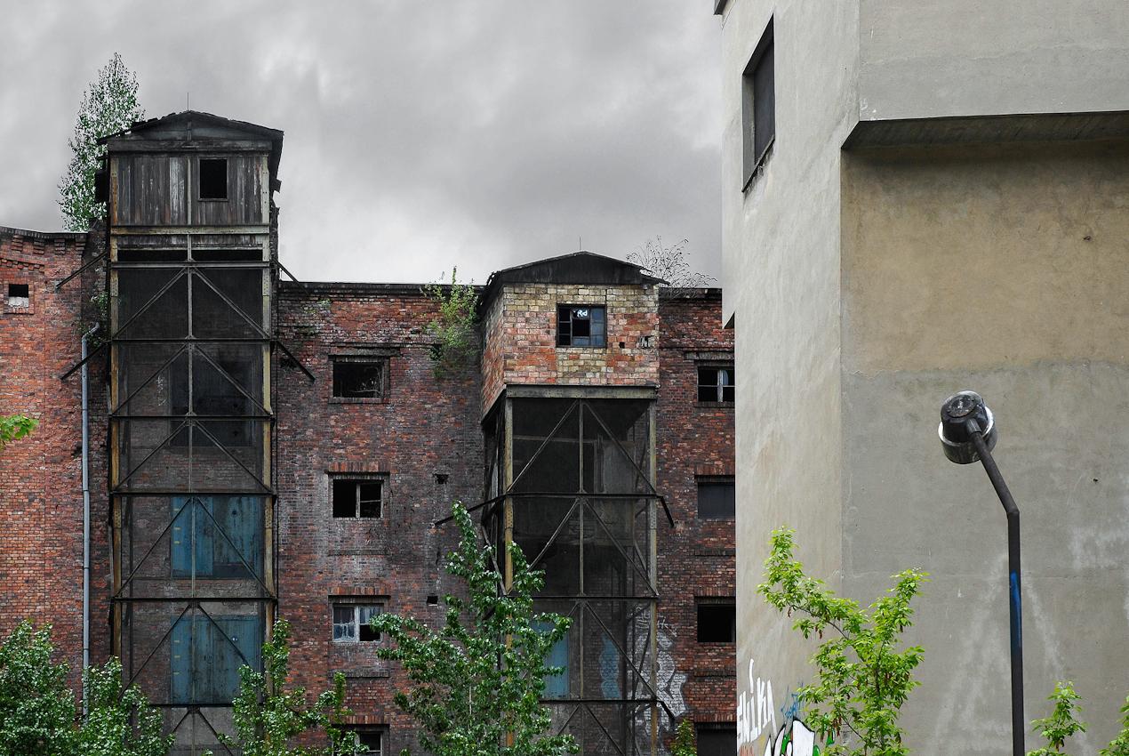 Blick von Osten auf zwei Kühlhauser des historischen Bauensembles Eisfabrik Luisenstadt in der Köpenicker Straße 40/41 in Berlin Mitte. Der Maihimmel wird durch dichte graue Wolken beherrscht. Die schlichten, funktionalen Lochfassaden mit Bauschmuck im Traufbereich werden durch zwei offene Lastenaufzüge dominiert. Die zwischen 1893 und 1922 errichteten und seit 1995 leer stehenden roten Backsteinbauten dienten der klimatisierten Lagerung von Kunsteis für Industrie, Handel, Gastronomie und Sporteisbahnen. Wilder Bewuchs an den Fassaden und auf dem Dach zeigt die Sanierungsbedurftigkeit der Architektur. Rechts im Vordergrund ist ein geschlossener, grau verputzter weiterer Lastenaufzug aus der Nutzungszeit der DDR und eine aus gleicher  Zeit stammender Lampenmast zu erkennen. Die Immobilie mit den historischen Produktions- und Lagergebäuden der früheren Norddeutschen Eiswerke AG unterliegt aufgrund ihrer attraktiven Lage direkt am Spreeufer einem hohen Spekulationsdruck. Die seit 1995 mit der Verwaltung und Entwicklung der Immobilie betraute Treuhand Liegenschaftsgesellschaft mbH strebt mit wachsendem Eifer die Zerstörung des  denkmalgeschützten Bauensembles an, um hier Platz für profitable Neubauten zu schaffen.(Weitere Informationen unter: http://de.wikipedia.org/wiki/Eisfabrik_%28Berlin-Mitte%29#cite_note-6)