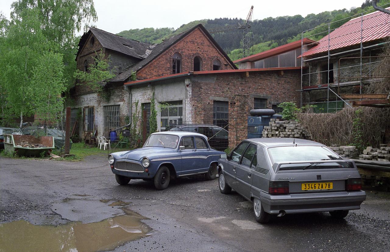 """Teilansicht der Nieverner Hutte auf der heute zu Fachbach an der Lahn gehörenden Insel Oberau. Fachbach ist eine Ortsgemeinde im Rhein-Lahn-Kreis in Rheinland-Pfalz und liegt an der ,,Baderstraße"""" (bei Lahn-Kilometer 128) an der Grenze zwischen Taunus und Westerwald. Die Nieverner Hütte ist eine ehemalige Eisenhütte (1671-1932) und seit 1892 anerkanntes Industriedenkmal.  Heute werden die Gebäude der Insel Oberau von verschiedenen Kleinbetrieben genutzt. In einem Gebäudetrakt befinden Werkstatt und Lager von Stefan Schutzenhofer, der seit 1983 einen Teile- und Reparaturservice für klassische RENAULT's betreibt. Ein SIMCA Aronde P 60 (Bj. 1959), der aus einer Sammlung übernommen wurde, steht zum Vergasereinbau bereit."""