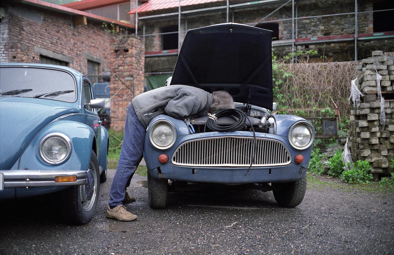 Stefan Schutzenhofer beim Einbau eines neuen Vergasers an einem SIMCA Aronde P 60 (Bj. 1959), der aus einer Sammlung mitubernommen wurde. Im Hintergrund sind Gebäudeteile der Nieverner Hütte zu erkennen. Zwischenzeitlich wurde ein VW-Käfer wahrend eines Kundenbesuches bei der benachbarten VW-Oldtimer-Werkstatt geparkt.