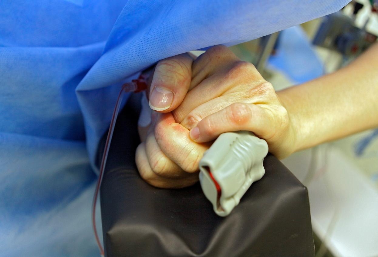 Prof. Dr. med. Thomas Hupp operiert Waldemar Goetz im Klinikum Stuttgart, OP-Saal 4 unter örtlicher Betäubung an der Halsschlagader. Anästhesistin Dr. Barbara Winghofer kümmert sich während der Operation um den Patienten Waldemar Goetz. Sie hält seine Hand.