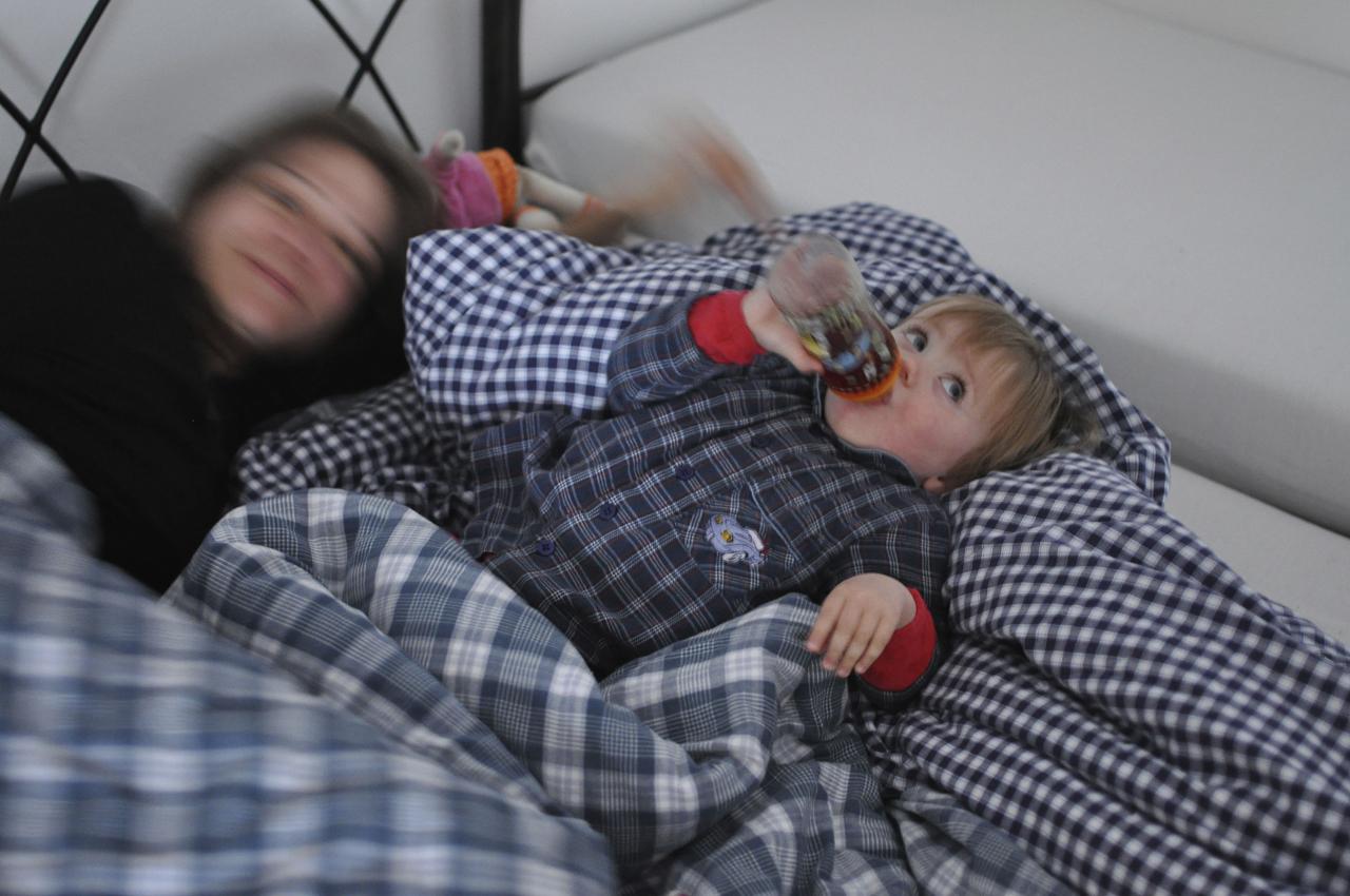 """Ein neuer Tag in Garching an der Alz beginnt. Die 18 Monate alte Magdalena ist gerade aufgewacht und trinkt ihr """"Wachwerdefläschchen"""". Im Hintergrund ihre Mutter Maria, die froh ist wenn Magdalena alle Zähne hat und die Nächte ruhiger werden. Magdalena wohnt mit ihrem Bruder Michael und ihren Eltern in Bayern in Garching an der Alz."""