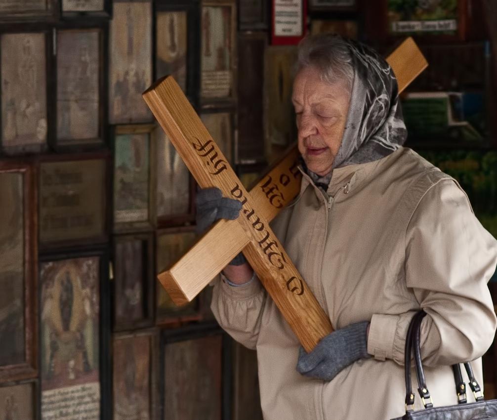 """Eine in Andacht versunkene alte Frau trägt ein Kreuz im Umgang der Gnadenkapelle in Altötting, in der die """"schwarze Madonna von Altötting"""" aufbewahrt ist und zu der jedes Jahr rund eine Million Menschen pilgern. Unter den Pilgern ist es Brauch, mit den eigens dazu bereitgestellten Kreuzen die Kapelle zu umrunden. Dabei werden sie nicht selten von Touristen und anderen Pilgern behindert, die die über 2.000 Votivtafeln im Umgang der Kapelle studieren, welche ein lebhaftes Zeugnis der Volksfrommigkeit geben."""