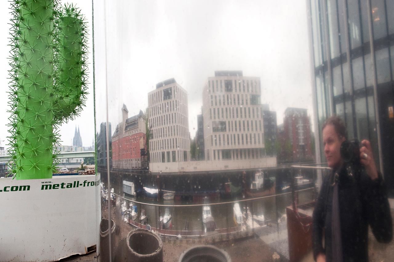 Die Fotografin Barbara Siewer spiegelt sich in einer Säule auf dem Rheinau-Baustellengelände. Zwischen dem mittleren und dritten, im Bau befindlichen Krahnhaus. Im Bild erkennt man außerdem einen künstlichen Kaktus als Werbeträger einer Baufirma. Fotografiert um 08:15 Uhr.