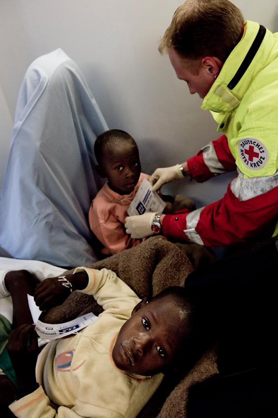 Ein Mitarbeiter des DRK kontrolliert die Namen zweier Kinder in einem Rettungswagen.