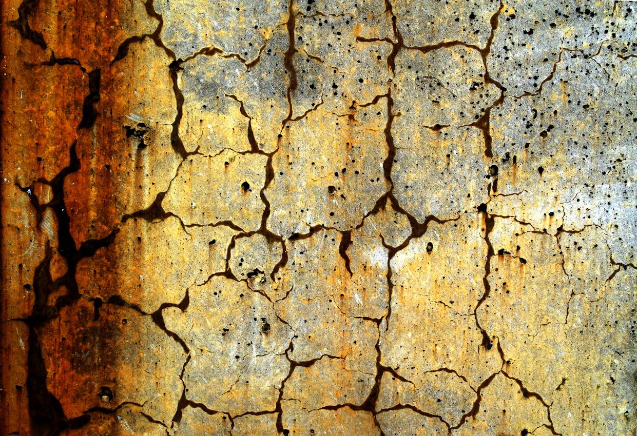 15:03 Uhr - Muster in einer Betonmauer am Karlsruher Rheinhafen. Bestandteile der rostenden Metallträger in der Mauer treten durch Risse und Löcher an die Oberfläche.