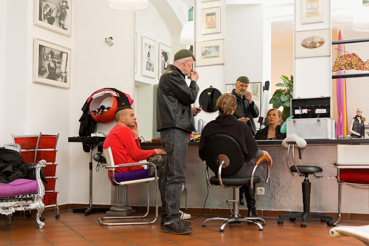 Der Friseur Ciro Boschetto, eine Kundin, sein Assistent Andrea Acciarino und eine Puppe im Geschäft des Friseurs in der Gabelsbergerstraße 36 in München.