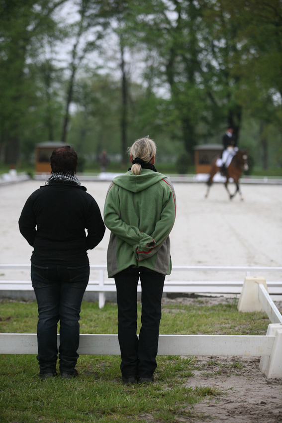 Zwei Turnierhelferinnen stehen am Dressurviereck, um den Teilnehmern beim Ein- und Ausritt zu helfen.